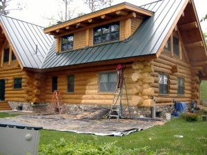 A log home being sand blasted.