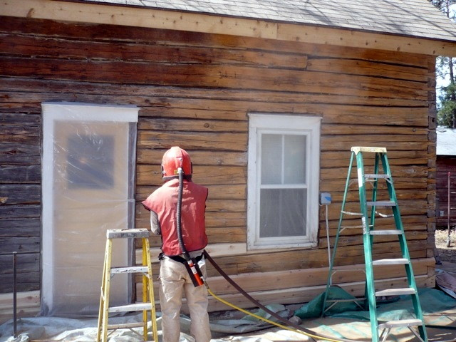 A log home that is partially blasted clean; showing the improvement.