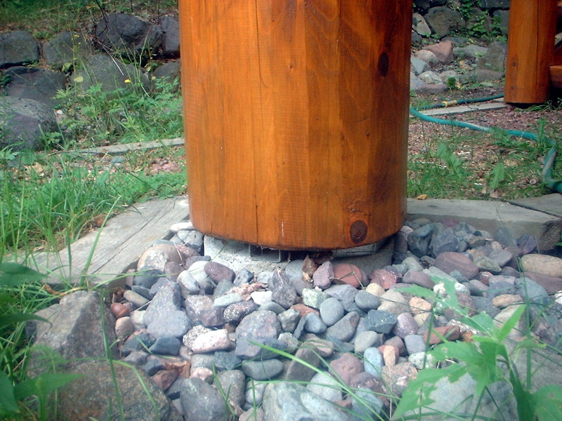 A new cedar log post that sits off the ground on a metal plate.