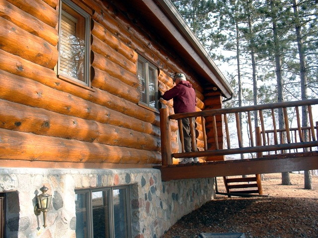 Log home that looks dull due to stain wearing thin in places.