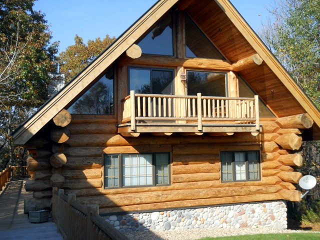 A log home stained with a light colored semi-transparent stain.