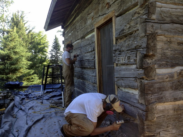 Two people working to remove mortar chinking on a log home.