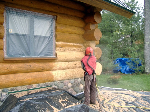 A person sand blasting old stain off of a wood home.