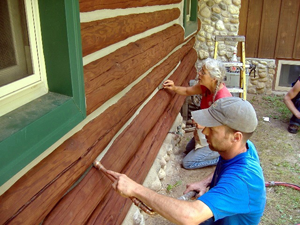 Chinking being applied carefully to a log home.