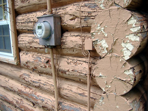 A log cabin with damaged peeling paint.