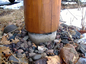 A log post correctly installed on a spacer to keep it off the ground and away from moisture.