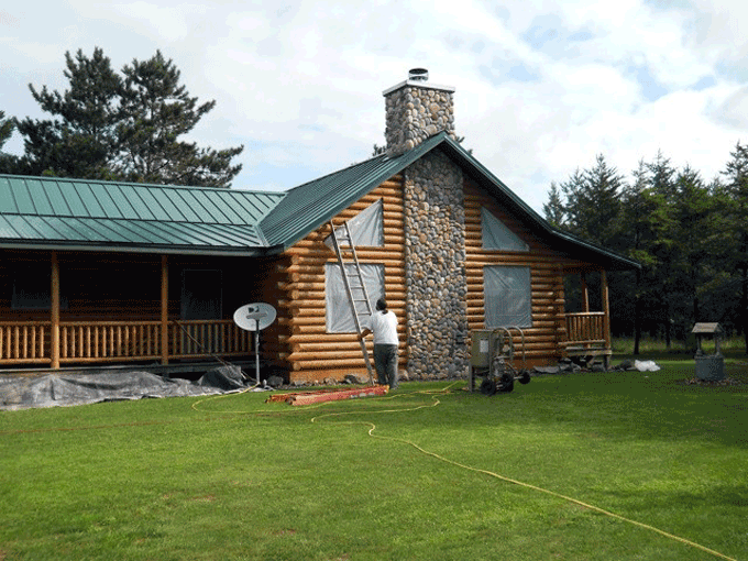 A log home showing signs that it is in need of blasting off the old stain and refinishing it.