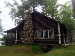 Log home with stone chimney