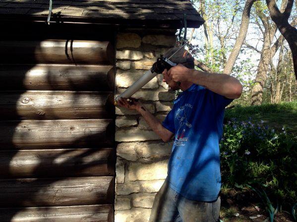 Applying chink caulk to logs