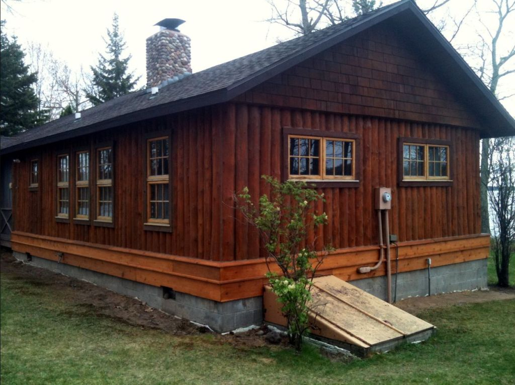 Newly replaced and stained vertical log cabin walls